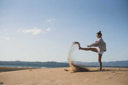 Teenage girl throwing sand on the beach - ACPF00166