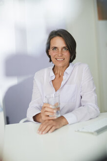 Portrait of mature businesswoman with glass of water sitting at desk - PNEF00844