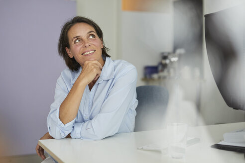 Portrait of smiling mature businesswoman sitting at desk in an office looking up - PNEF00847