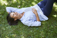 Portrait of mature woman relaxing on a meadow - PNEF00856