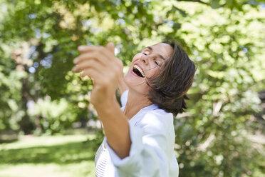 Happy mature woman dancing in nature - PNEF00859
