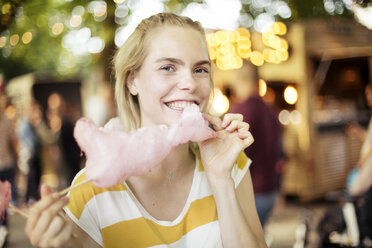 Portrait of young woman eating pink candy floss on streetfood festival - JESF00006
