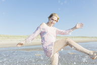 Netherlands, young woman splashing water at the beach in summer - JESF00012