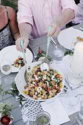 People around a table at a garden party, a bowl of salad. - MINF06018