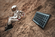 Spaceman sitting on nameless planet, charging device with solar panel - VPIF00451