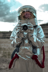 Spaceman on nameless planet taking pictures with camera - VPIF00472