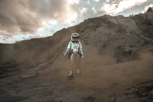 Spaceman exploring nameless planet, walking in a dust cloud - VPIF00475