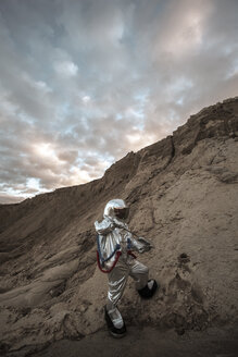 Spaceman on nameless planet taking samples of sand - VPIF00493