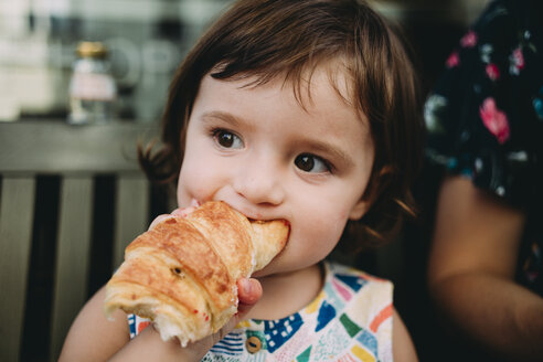 Portrait of baby girl eating a croissant - GEMF02243