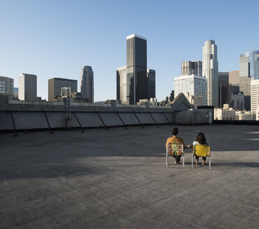 A couple, man and woman sitting in deck chairs on a rooftop overlooking city skyscrapers. - MINF06050