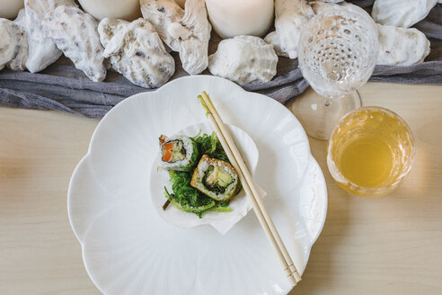 Overhead view of plates of sushi and a table setting for a celebration meal. - MINF06107