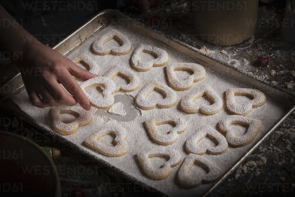 Valentine S Day Baking Woman Arranging Heart Shaped Biscuits On A Baking Tray Minf06164 Mint Images Westend61