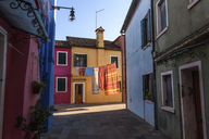 Narrow alley with colourful facades and clothes on washing line in Venice, Italy. - MINF06494