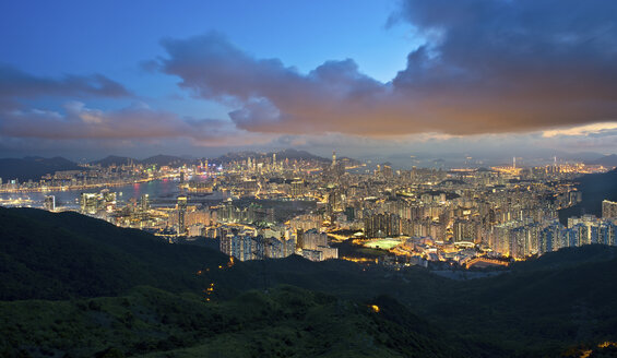 View across Kowloon with city of Hong Kong with illuminated skyscrapers at dusk. - MINF06527