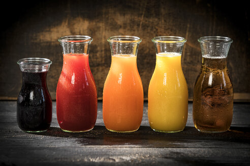 Row of five glass bottles of various fruit juices - MAEF12683