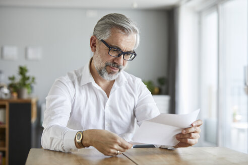 Portrait of mature man reading letter at home - RBF06472