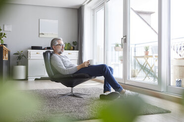 Mature man sitting on leather chair in his living room relaxing with cup of coffee - RBF06475