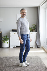 Portrait of smiling mature man standing in his living room - RBF06481
