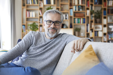 Portrait of smiling mature man relaxing on couch at home - RBF06484