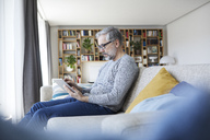 Mature man sitting on couch at his living room using tablet - RBF06487