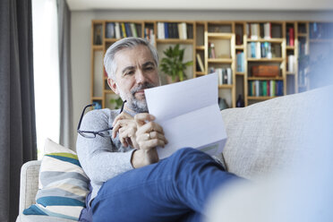 Mature man sitting on couch at home reading letter - RBF06490