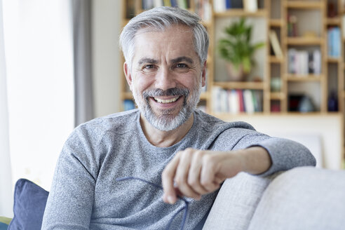 Portrait of smiling mature man sitting on couch at home - RBF06493