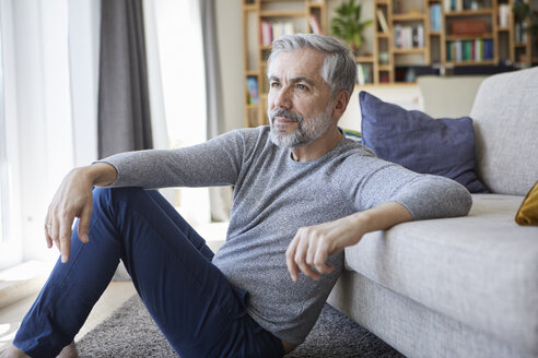 Mature man sitting on floor of his living room looking out of window - RBF06496