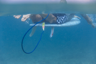 Maledives, Indian Ocean, surfer lying on surfboard, underwater shot - KNTF01184