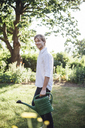 Man with watering can in garden - JESF00021