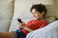 Portrait of laughing little girl lying on the couch looking at cell phone - JSMF00387