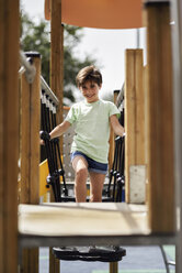 Portrait of smiling little girl having fun on a playground - JSMF00399