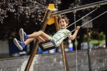 Portrait of happy little girl having fun on a swing - JSMF00402