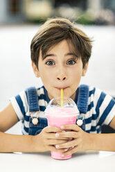Portrait of little girl drinking strawberry milkshake at pavement cafe - JSMF00408