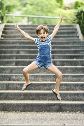 Portrait of screaming little girl jumping in the air outdoors - JSMF00417