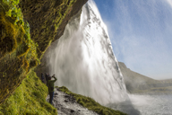 People standing on a narrow path underneath a waterfall cascade over a sheer cliff. - MINF06577
