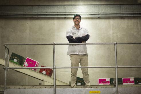 Worker standing in apple factory - ZEF15934