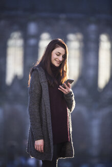 Portrait of smiling young woman looking at cell phone in autumn - JESF00039