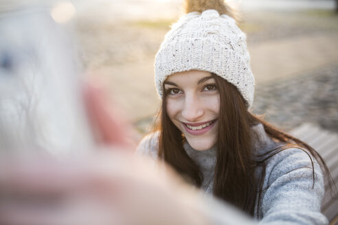 Portrait of smiling young woman taking selfie with smartphone in winter - JESF00045