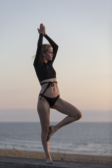 Young blond woman doing yoga at the beach in the evening, tree position - JESF00075