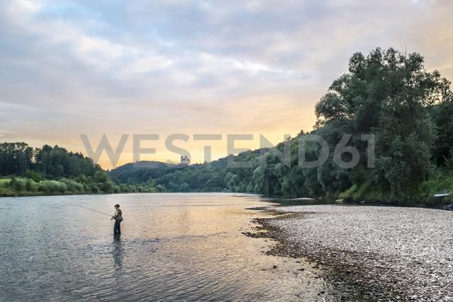 Germany, Upper Bavaria, Burghausen, Salzach valley, fly fisherman at sunset - HAMF00347
