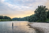 Germany, Upper Bavaria, Burghausen, Salzach valley, fly fisherman at sunset - HAMF00347