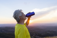 Spain, Catalonia, Montcau, senior man drinking water and looking at view from top of hill during sunset - AFVF01355