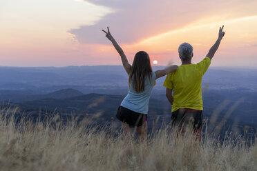 Spain, Catalonia, Montcau, happy senior father and adult daughter looking at view from top of hill during sunset - AFVF01358