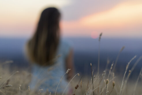 Spain, Catalonia, Montcau, grasses in sunset with blurred woman in background - AFVF01361