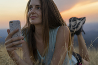 Smiling young woman with cell phone lying in grass during sunset - AFVF01364