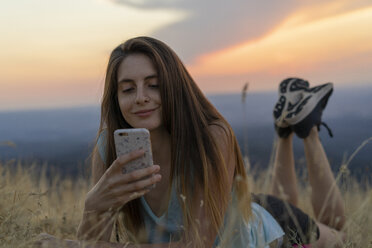 Smiling young woman using cell phone lying in grass during sunset - AFVF01367