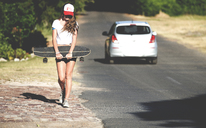 Young woman walking beside a road carrying a skateboard. - MINF06626