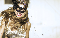 Young woman wearing a black face mask at a party with confetti falling. - MINF06638