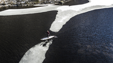 Aerial view of a paddleboarder carrying his board standing on a block of ice on an ice floe in an inlet in the Lofoten Islands, Norway. - MINF06647