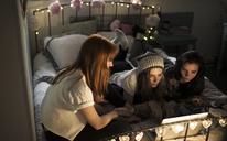 Young women on a bed watching a laptop screen. - MINF06650